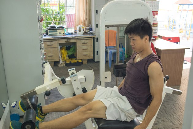 Man working out in a gym doing leg presses