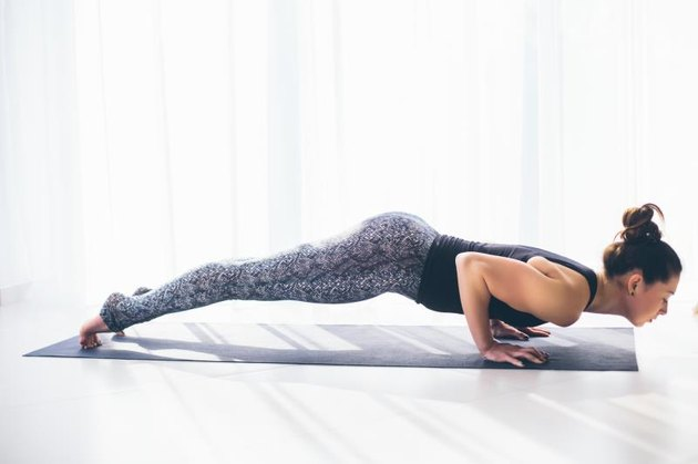 Chaturanga dandasana. Beautiful yoga woman practice in a training hall background. Yoga concept.