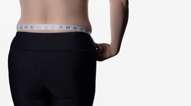 Woman measuring waist shown from the back