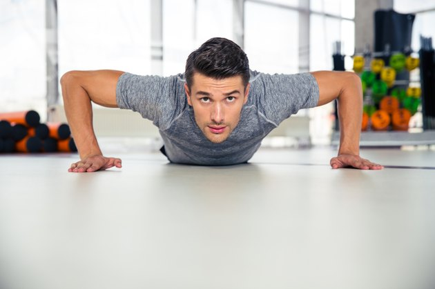 Handsome man doing push-ups in gym