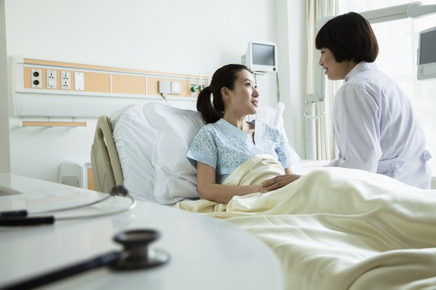 Female doctor sitting on hospital bed and discussing with young female patient