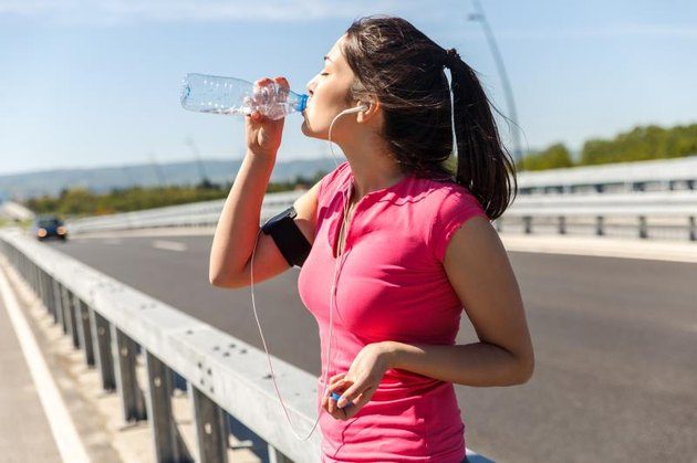 Young woman taking a break from exercising, She is drinking water