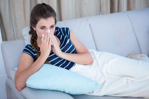 Sick woman blowing her nose on couch
