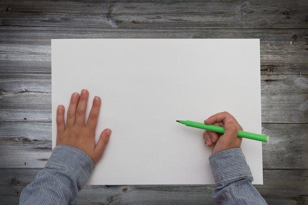 child holding pen over blank sheet of paper. kids hands