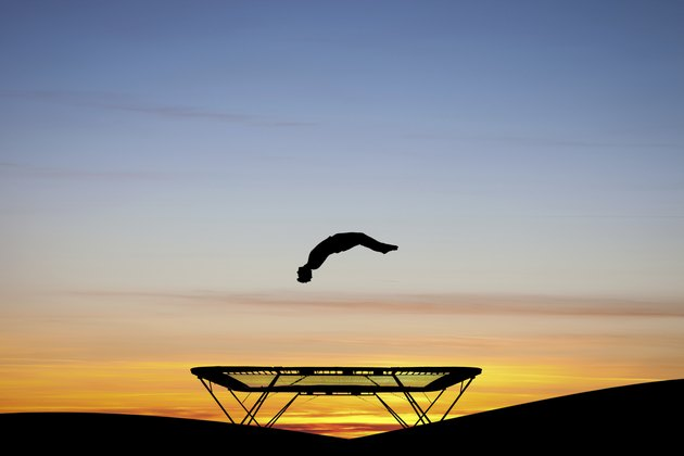 silhouetted gymnast on trampoline at sunset