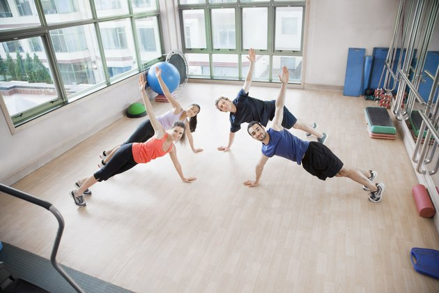 Four young people stretching and looking at the camera in an aerobics class
