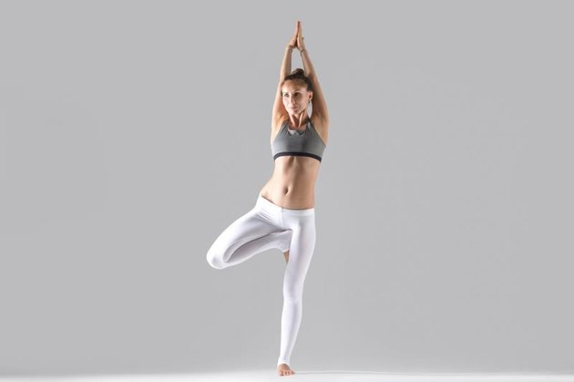 Young attractive woman practicing yoga, standing in tree exercise, Vrksasana pose, working out wearing sportswear, indoor full length, isolated, grey studio background