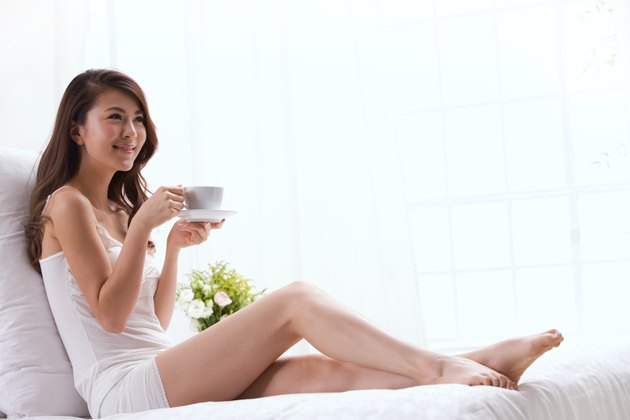 Young lady drinking coffee on bed