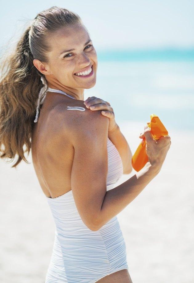 happy young woman applying sun block creme on beach