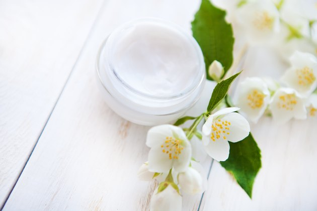Pot of beauty cream with flower on white wooden table