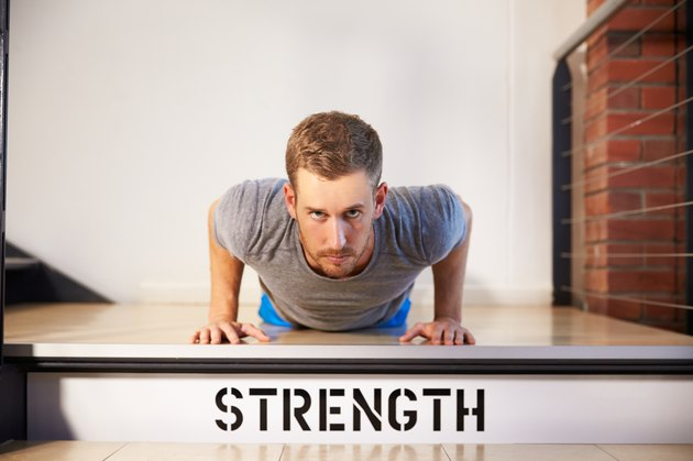Man In Gym Doing Press-Ups On Step Labeled Strength