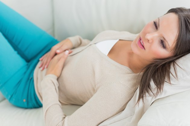 Sick woman lying on sofa with stomach ache