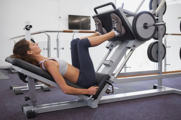 Fit woman using weights machine for legs