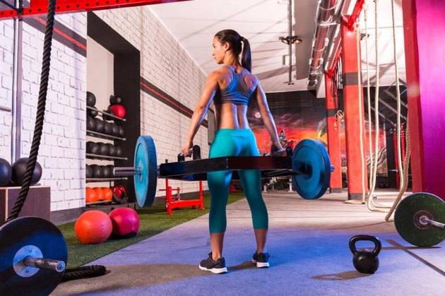 An athletic woman in a gym holds a shrug bar, preparing for shoulder shrugs or deadlifts.