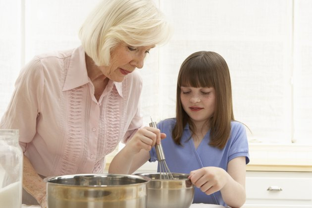 Granddaughter (8-10) and grandmother mixing ingredients in bowl