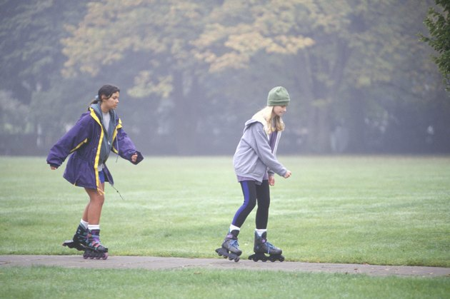 Two teenage girls (13-14) in-line skating in park, (Side view)