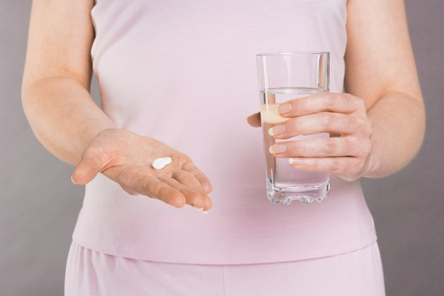 Woman holding pills and glass of water
