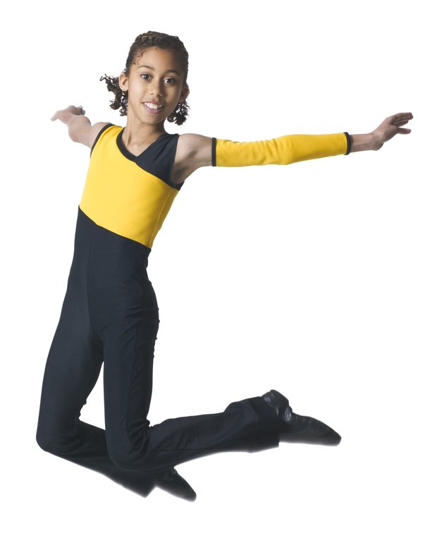 an african american girl in a black and yellow dance outfit jumps through the air