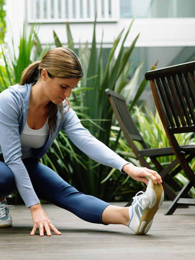 Woman wearing running clothes performing leg stretch in garden