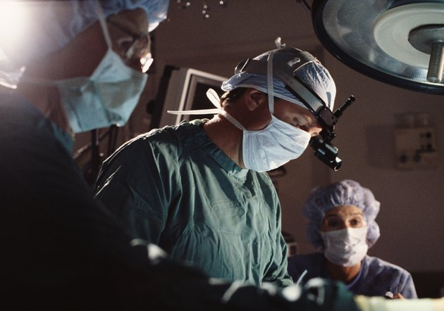 a group of doctors and nurses perform surgery in an operating room