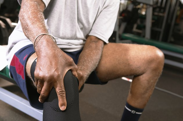 Senior man in gym wearing knee strap, holding knee, close-up