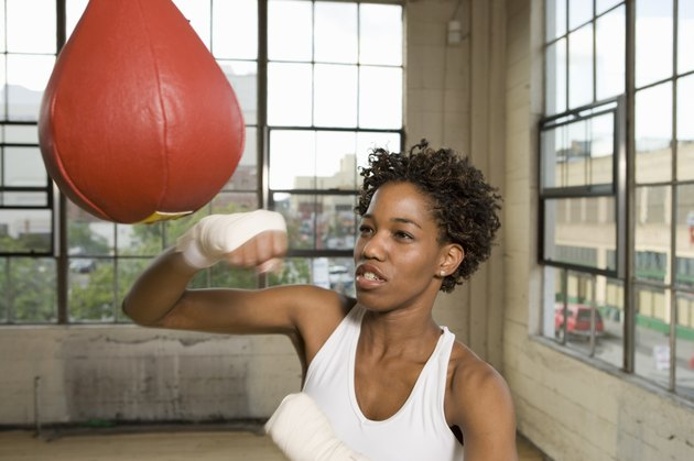 Woman exercising with punching bag in gym