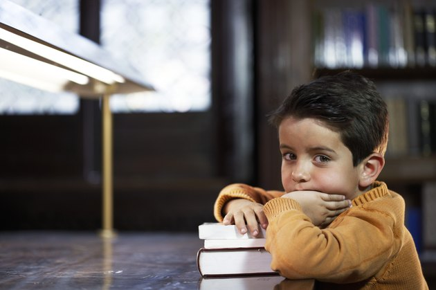 Boy (5-7) sitting at library table, resting arm on books, portrait