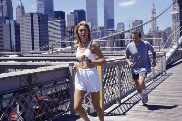 USA, New York City, woman and man jogging on Brooklyn Bridge