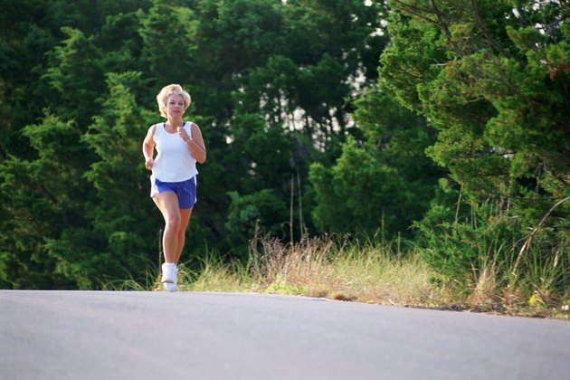 Woman jogging on side of road