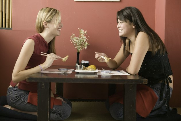 Two teenage girls (16-17), eating in restaurant