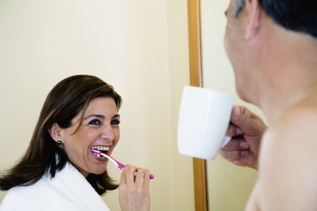 Middle-aged couple brushing teeth and drinking coffee in morning