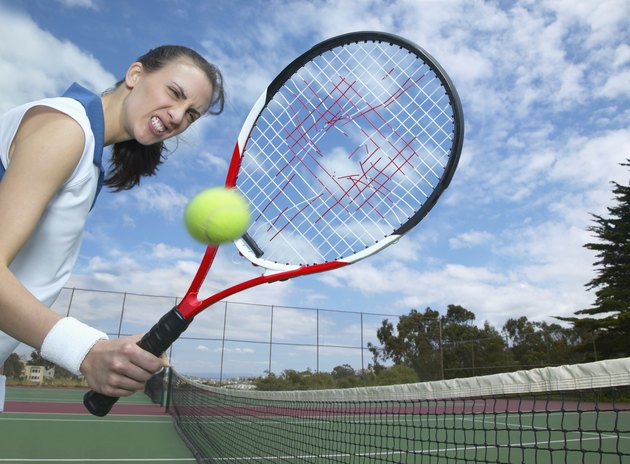 Woman holding tennis racket with hole in it and tennis ball in air