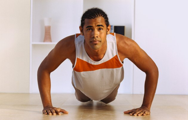 Portrait of a young man doing push ups on the floor