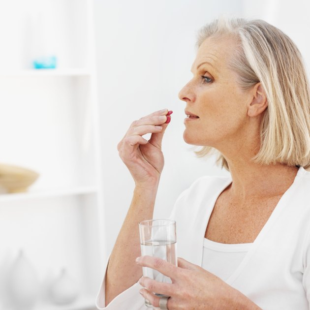 Side view of mature woman holding glass of water and taking pills