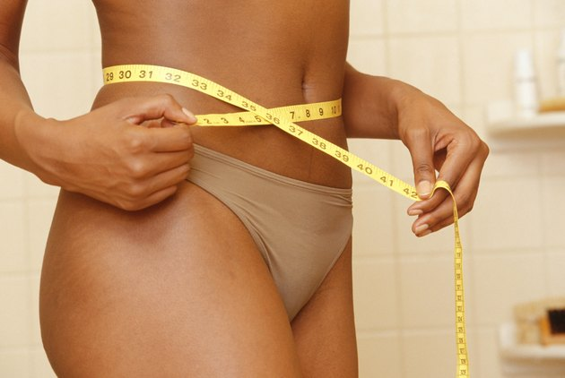 Woman measuring waistline in bathroom, mid section, close-up