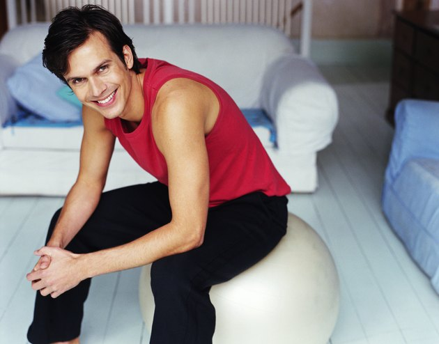 Man sitting on fitness ball in living room, smiling, portrait