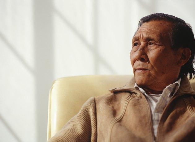 Senior man sitting indoors in armchair
