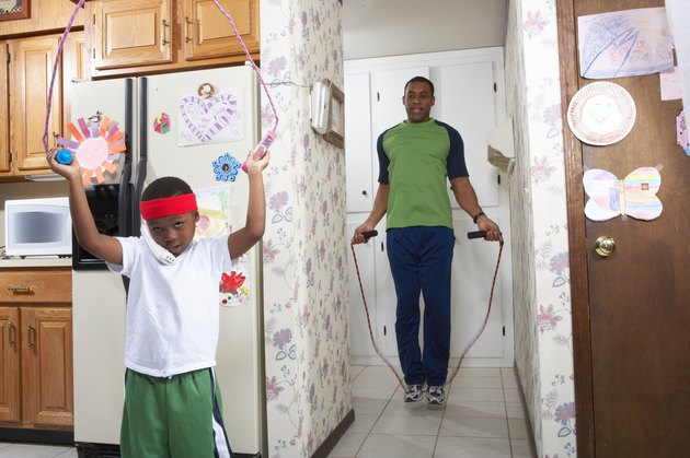 Father and son (4-5) exercising with skipping rope in house