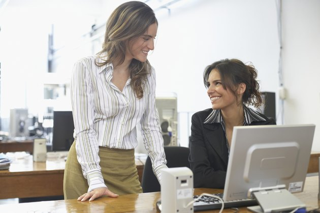 Two businesswomen talking to each other in an office