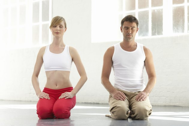 Man and woman kneeling, eyes closed
