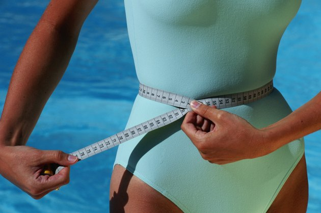 Woman with measuring tape around waist, mid section