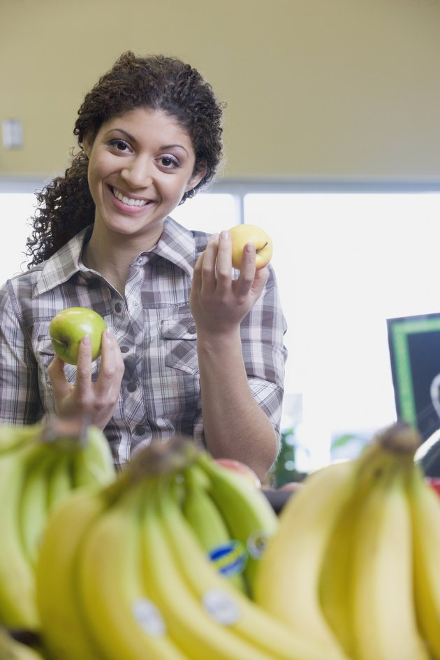Mixed Race woman choosing apples at grocery store