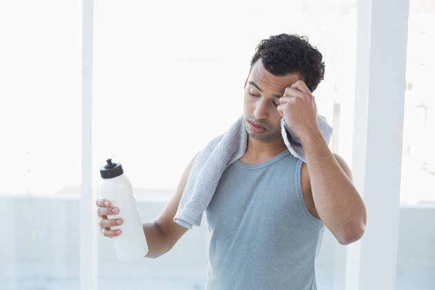 Man wiping sweat with towel in fitness studio