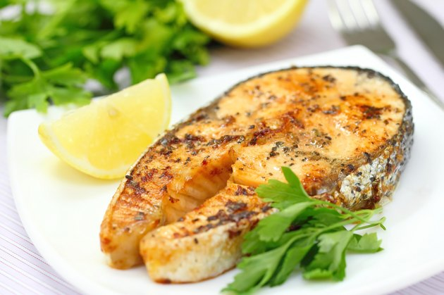 Roasted salmon with lemon and greens on the white plate
