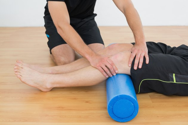 Man getting his knee examined by a physical therapist