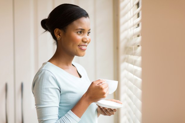 african woman drinking coffee near the window