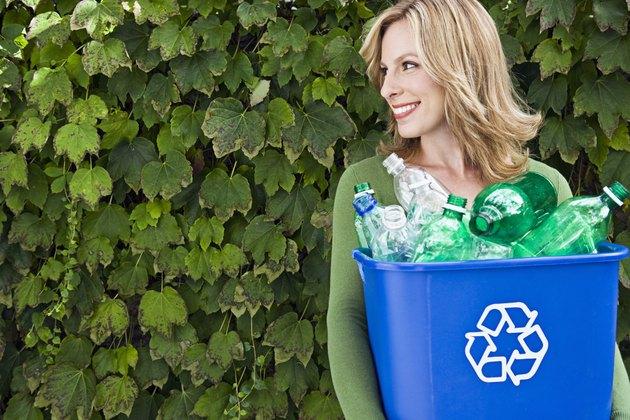 Smiling woman carrying recycling bin