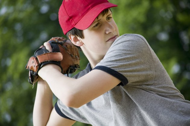 Teenage boy pitching baseball