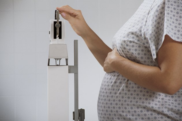 Pregnant woman weighing herself on hospital scale