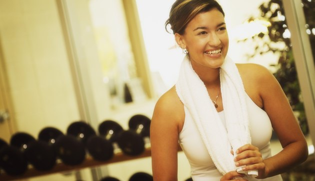 A young woman in a fitness facility smiling